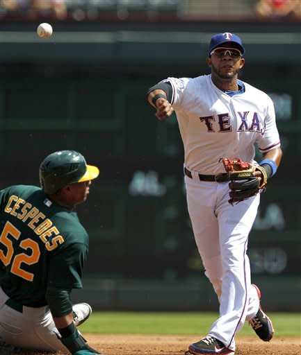 Texas Rangers shortstop Elvis Andrus, right, makes the throw to first for the double play after forcing out Oakland Athletics' Yoenis Cespedes in the first inning of a baseball game, Thursday, Sept. 27, 2012, in Arlington, Texas. The Athletics' Chris Carter was out at first. (AP Photo/Tony Gutierrez)