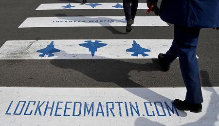 FILE PHOTO - Trade visitors are seen walking over a road crossing covered with Lockheed Martin branding at Farnborough International Airshow in Farnborough, Britain, July 17, 2018. REUTERS/Toby Melville/File Photo