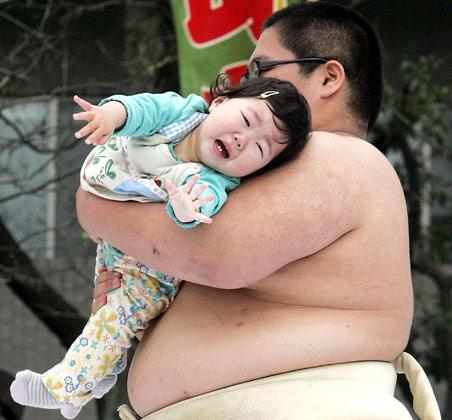 TOKYO, JAPAN - APRIL 29: Sumo wrestler students try to make babies cry during the Crying Sumo competition at Sensoji Temple on April 29, 2006 in Tokyo, Japan. The first baby that cries wins this competition. The ceremony has been taking place in Japan to wish for the good health of the child as it is said that crying is good for the health of babies. Majority of the children who participate are less than 1 year old. (Photo by Junko Kimura/Getty Images)