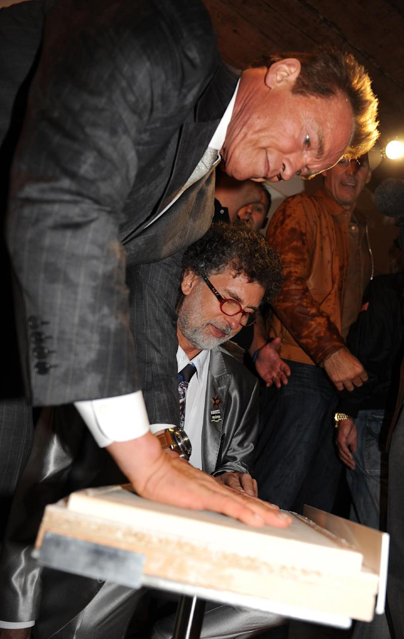 In this picture publicly provided by the Arnold Schwarzenegger museum on their web page www.arnieslife.com, Austrian-born actor and former Californian governor, Arnold Schwarzenegger, makes a print of his hands during the inauguration of a museum in the house of Schwarzenegger's birth in Thal near Graz, Austria Friday Oct. 7, 2011. (AP Photo/dapd/ HO/www.arnieslife.com) - MANDATORY CREDIT - EDITORIAL USE ONLY -