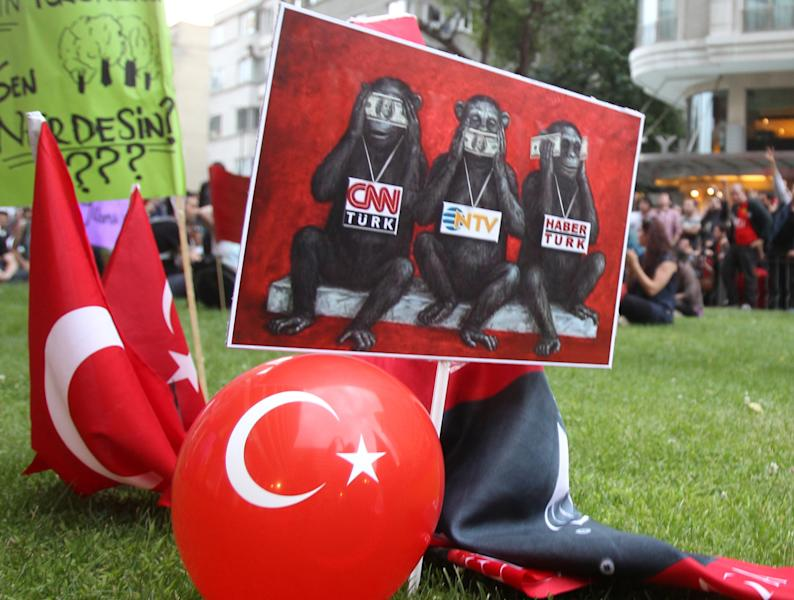 In this Sunday, June 2, 2013 photo protesters display a banner depicting Turkish media as the three wise monkeys who see no evil, speak no evil and hear no evil, outside Haber Turk television channel in Istanbul. As Turkey's largest city was convulsed by some of the most widespread anti-government protests the country has seen in modern times, the country's broadcast media looked away. Dense clouds of acrid, choking tear gas might have been blanketing the central square of Turkey's largest city, but it was penguins that were the theme of the evening on one of the country's largest private television stations. Its nature documentary ran uninterrupted, while another channel opted for a cooking show and a documentary on Adolf Hitler. (AP Photo/Thanassis Stavrakis)