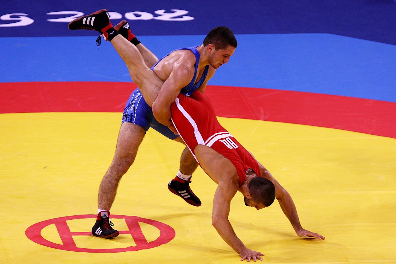 BEIJING - AUGUST 20:  Andriy Stadnik of the Ukraine (blue) wrestles Leonid Spiridonov of Kazakhstan during the Men's Freestyle 66kg Semifinals wrestling event at the China Agriculture University Gymnasium during Day 12 of the Beijing 2008 Olympic Games on August 20, 2008 in Beijing, China.  (Photo by Al Bello/Getty Images)