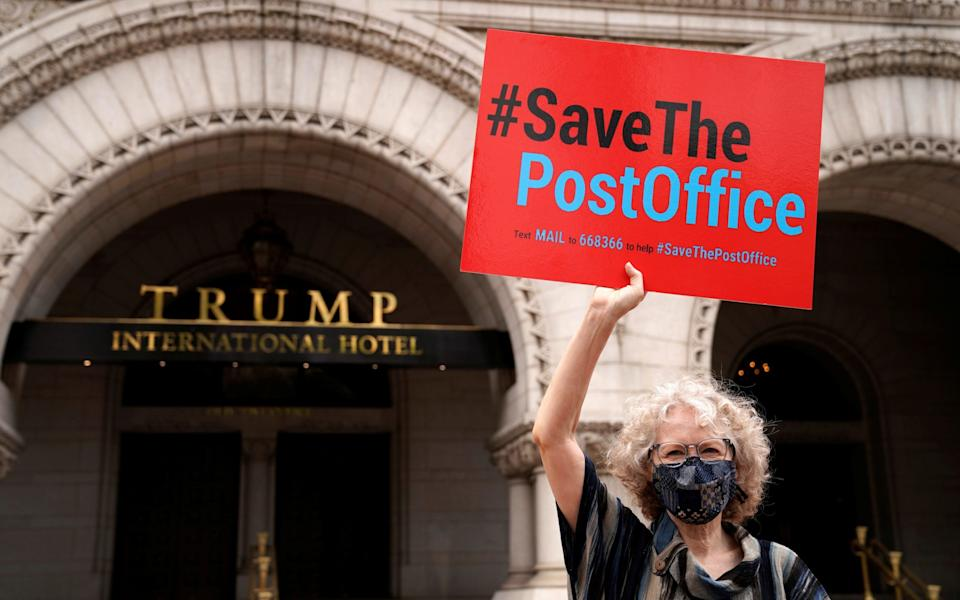 A protester holds up a sign in support of the US Postal Service outside the Trump Hotel in Washington DC - Erin Scott/Reuters