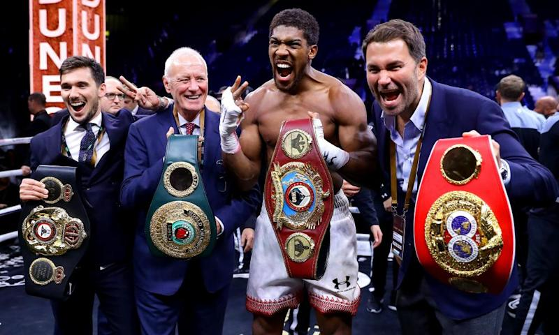 Belting up: Anthony Joshua celebrates regaining his heavyweight titles flanked by Eddie and Barry Hearn, Clash on the Dunes, December 2019, Diriyah, Saudi Arabia.