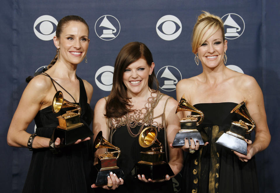 """FILE - In this Feb. 11, 2007 file photo, musicians Emily Robison, left, Natalie Maines, center, and Martie Maguire of the group The Dixie Chicks pose with their awards for song of the year, for record of the year, for album of the year, for best country album, and for best country performance at the 49th Annual Grammy Awards in Los Angeles. The Grammy-winning country group, who recently changed their name to The Chicks, have a new album """"Gaslighter"""" out July 17, 2020. (AP Photo/Kevork Djansezian, File)"""