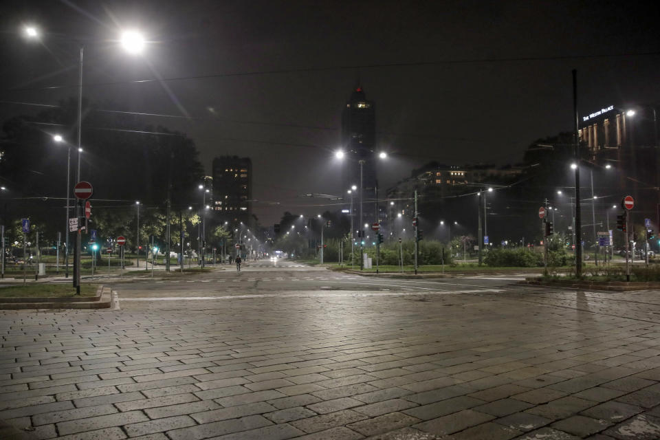 An empty street is lit by street lights in Milan, northern Italy, Sunday, Oct. 25, 2020. Since the 11 p.m.-5 a.m. curfew took effect last Thursday, people can only move around during those hours for reasons of work, health or necessity. (AP Photo/Luca Bruno)