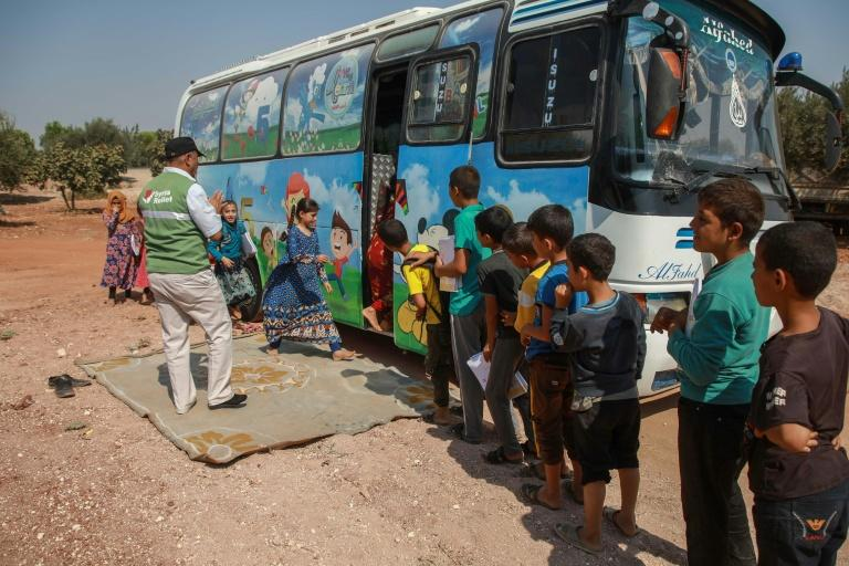 Displaced Syrian children queue for school outside a converted bus in the country's northwest – a makeshift solution to the war-induced closure of formal facilities (AFP Photo/Aaref WATAD)
