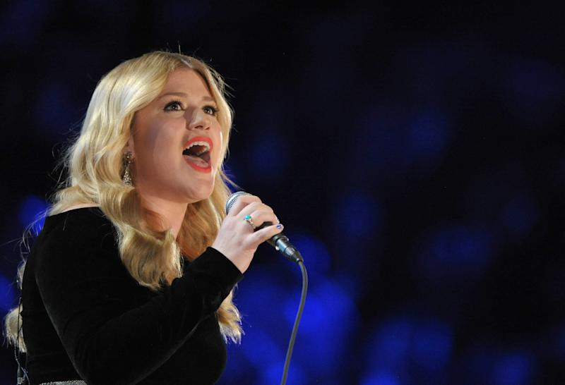 "FILE - In this Feb. 10, 2013 file photo, Kelly Clarkson performs on stage at the 55th annual Grammy Awards, in Los Angeles. NBC says Robin Williams, Whoopi Goldberg and William Shatner are among those joining Kelly Clarkson's holiday special. The special, titled ""Kelly Clarkson's Cautionary Christmas Music Tale,"" also is set to include country stars Blake Shelton, Reba McEntire and Trisha Yearwood, NBC said Wednesday, Nov. 20. Clarkson's special is scheduled to air 10 p.m. EST Dec. 11 on NBC. (Photo by John Shearer/Invision/AP)"