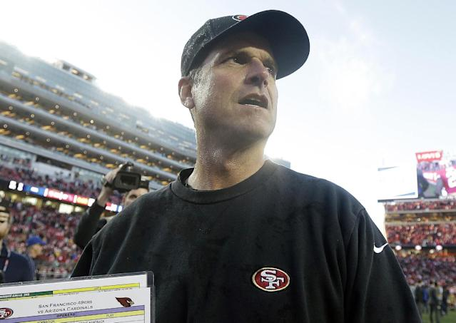 FILE- In this Dec. 28, 2014, file photo, San Francisco 49ers head coach Jim Harbaugh walks off the field after an NFL football game against the Arizona Cardinals in Santa Clara, Calif. Harbaugh was in discussions with Michigan to return to his alma mater as its new football coach, a person with knowledge of the talks said Monday, Dec. 29. (AP Photo/Marcio Jose Sanchez, File)
