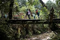 A Mexican woman who was sold into marriage crosses a bridge with her family in Metlatonoc