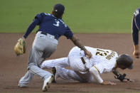 San Diego Padres third baseman Manny Machado (13) is tagged out by Seattle Mariners shortstop J.P. Crawford (3) as he's caught in a rundown between second and third during the first inning of a baseball game Saturday, Sept. 19, 2020, in San Diego. (AP Photo/Denis Poroy)