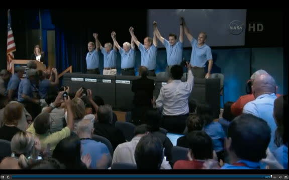 MSL press conference panelists raising arms in exultation following the succesful landing of Curiosity rover on Mars, August 5, 2012.