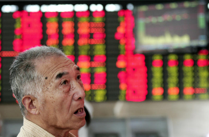 An investor looks at the stock price monitor at a private securities company Friday June 29, 2012 in Shanghai, China.  Asian stock markets and the euro rose sharply Friday after European leaders hammered out a strategy aimed at stanching an escalating financial crisis among the 17 countries that use the euro. (AP Photo)