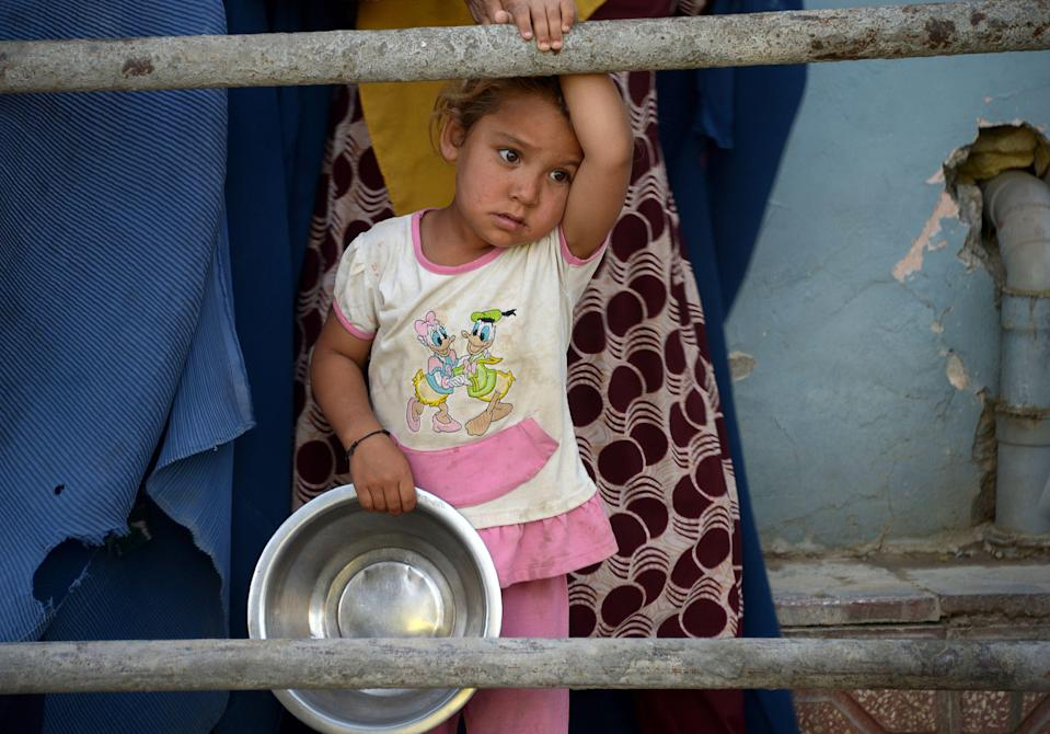 A young Afghan girl waits for food from private charity during Ramadan.