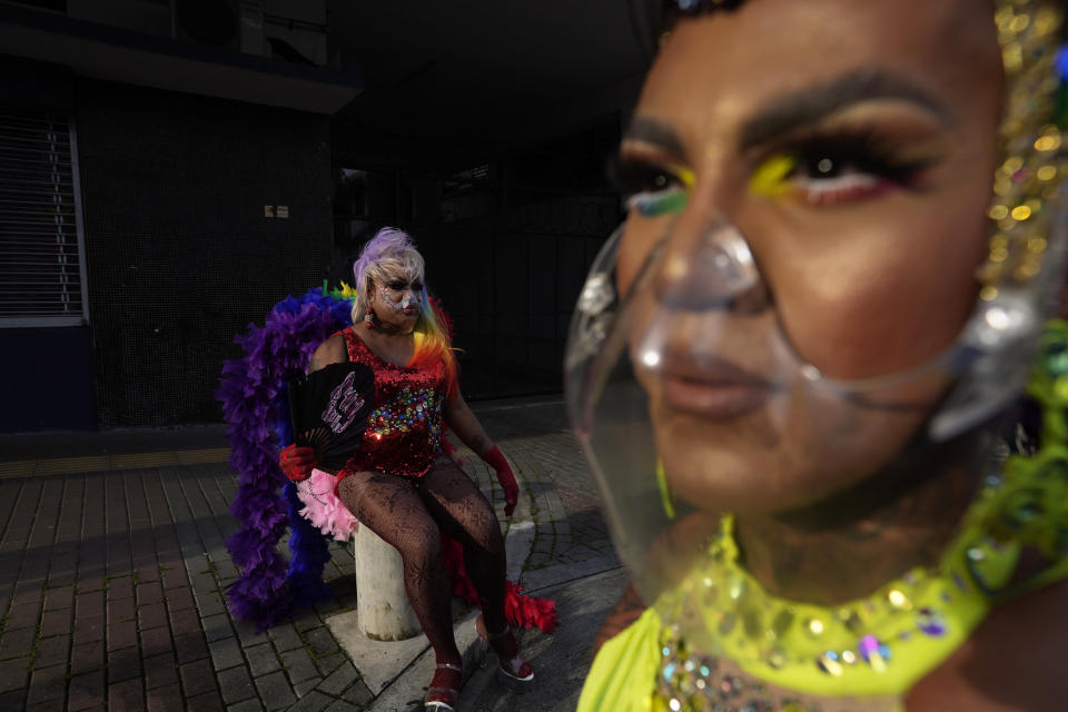 Drag queens, wearing protective face masks, take a break during the annual Gay Pride parade in Panama City, Saturday, June 26, 2021. (AP Photo/Arnulfo Franco)