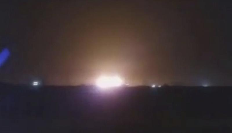 The Ukraine International Airlines flight is seen bursting into flames from a distance at night time.
