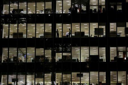 FILE PHOTO: Workers are seen in office windows in the financial district of Canary Wharf in London