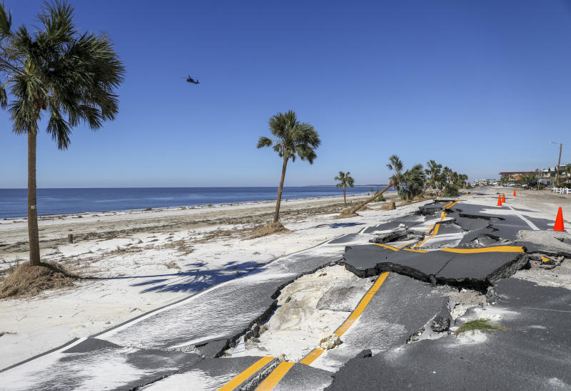 A helicopter flies along the coast as a portion of Highway 98 is seen crumbled Friday, Oct. 12, 2018 in Mexico Beach, Fla. Residents of the small beach town of Mexico Beach began to make their way back to their homes some for the first time after Hurricane Michael made landfall Wednesday. (Chris Urso/The Tampa Bay Times via AP)