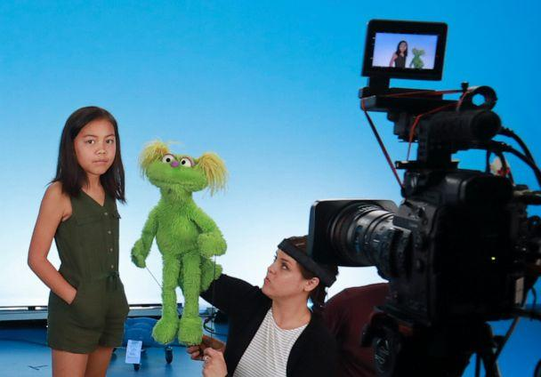 PHOTO: Salia Woodbury, 10, left, from Irvine, Calif., on the set with 'Sesame Street' muppet Karli and puppeteer Haley Jenkins during a taping about parental addiction in New York. (Bebeto Matthews/AP)