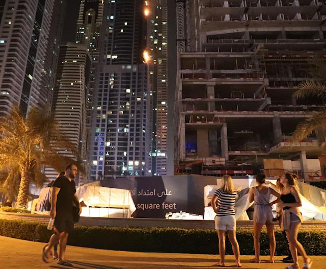 <p>People on a street view a fire at the 1,105 foot tall Torch tower skyscraper on August 4, 2017 in Dubai. (Photo: Karim Sahib/AFP/Getty Images) </p>