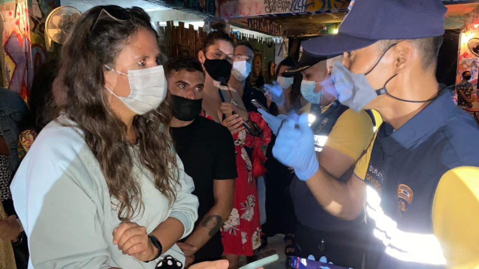In this Tuesday, Jan. 26, 2021, Thai immigration officers talk to people at a bar on Koh Phangan island, Surat Thani province, southern Thailand. Police raided a party at a bar on a popular resort island in southern Thailand and arrested 89 foreigners for violating coronavirus regulations, officials said Wednesday. (Police Investigation Team of Surat Thani Immigration via AP)