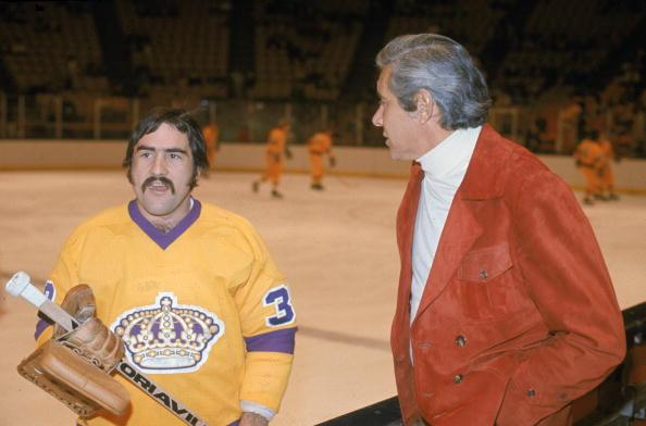 Canadian professional ice hockey player Rogatien 'Rogie' Vachon, goalie of the Los Angeles Kings, talks to a silverhaired gentleman on the sidelines before a game, Los Angeles, 1970s. Vachon played for the Kings from 1971 to 1978. (Photo by Bruce Bennett Studios/Getty Images)