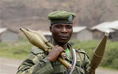 A Congolese armed forces (FARDC) soldier carries his weapons as he moves to a new position as they battle M23 rebels in Kibati, outside Goma in the eastern Democratic Republic of Congo, August 30, 2013. REUTERS/Thomas Mukoya