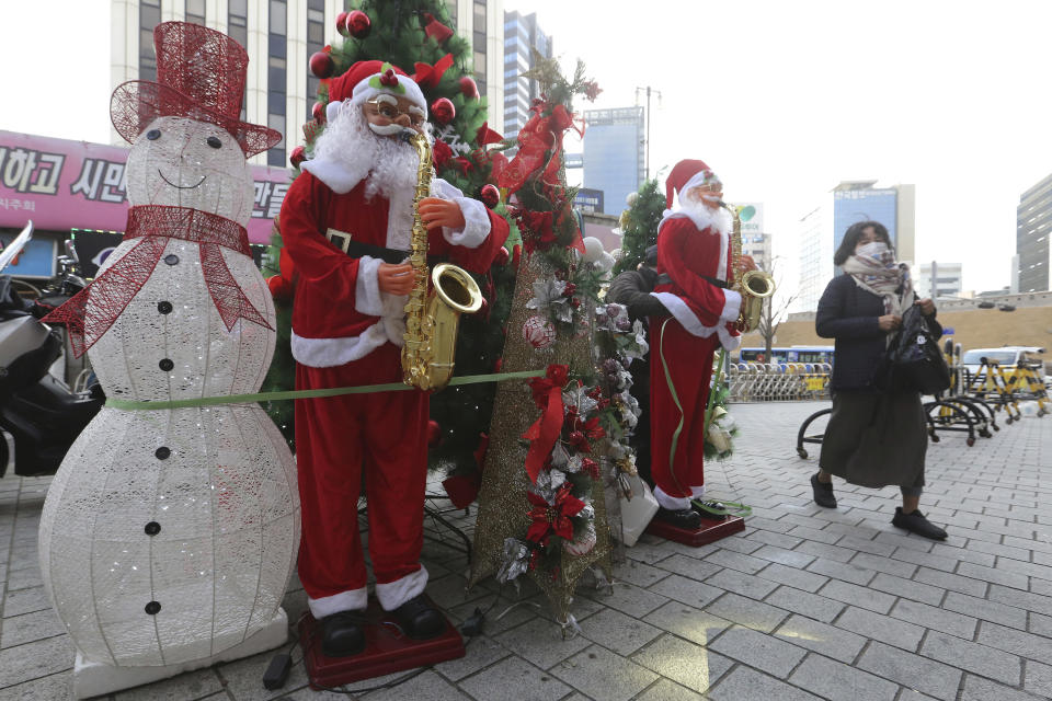A woman wearing a face mask as a precaution against the coronavirus passes by Christmas decorations outside a shopping mall in Seoul, South Korea, Friday, Nov. 27, 2020. South Korea's daily virus tally hovered above 500 for the second straight day, as the country's prime minister urged the public to stay home this weekend to contain a viral resurgence. (AP Photo/Ahn Young-joon)