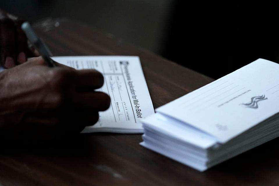 Philadelphia City Council President Darrell L. Clarke fills out an application for a mail-in ballot before voting at the opening of a satellite election office at Temple University's Liacouras Center in Philadelphia. Sept. 29, 2020.