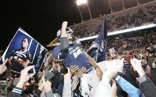 Utah State's Chuckie Keeton (16) celebrates with teammates and fans after defeating Toledo in an NCAA college football game on Saturday, Dec. 15, 2012, in Boise, Idaho. Utah State won the Famous Idaho Potato Bowl game 41-15. (AP Photo/Matt Cilley)