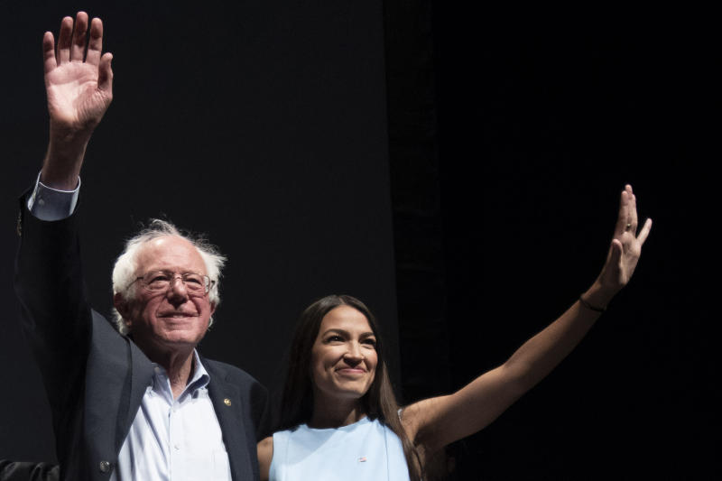 Sen. Bernie Sanders and Alexandria Ocasio-Cortez wave to the crowd at the end of a rally in Wichita, Kan., last year. (Photo: J Pat Carter for the Washington Post/Getty Images)