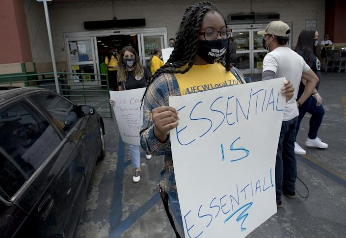 """Grocery workers associated with UFCW Local 770 demonstrate outside a Food 4 Less store in Los Angeles on Aug. 5 after workers at the store had reportedly become infected with the coronavirus. <span class=""""copyright"""">(Los Angeles Times)</span>"""