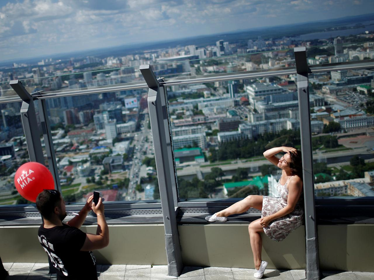 A woman poses for a picture at viewing point on the Vysotsky skyscraper in Yekaterinburg, Russia, July 28, 2017. REUTERS/David Mdzinarishvili