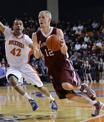 Laffayette's Seth Hinrichs (12) looks to the basket around Bucknell's Cameron Ayers (42) during the first half of an NCAA college basketball game for the Patriot League men's tournament title, Wednesday, March 13, 2013, in Lewisburg, Pa. (AP Photo/Ralph Wilson)