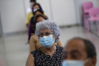 FILE - In this June 23, 2021, file photo, people wait in a recovery area after getting shots of the Johnson & Johnson vaccine at an inoculation center operated by the Portuguese armed forces at Lisbon University's sports stadium. Countries across Europe are scrambling to accelerate coronavirus vaccinations to outpace the spread of the delta variant in a high-stakes race to prevent hospital wards from filling up again with patients fighting for their lives. (AP Photo/Armando Franca, File)