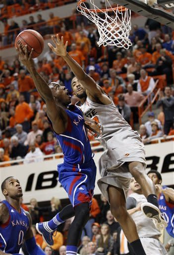 Kansas guard Tyshawn Taylor, left, shoots as Oklahoma State forward Michael Cobbins, right, defends duirng the first half of an NCAA college basketball game in Stillwater, Okla., Monday, Feb. 27, 2012. (AP Photo/Sue Ogrocki)