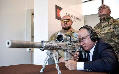 Russia's President Vladimir Putin (front) aims a rifle at the Kalashnikov shooting centre at Patriot military park - Credit: Tass