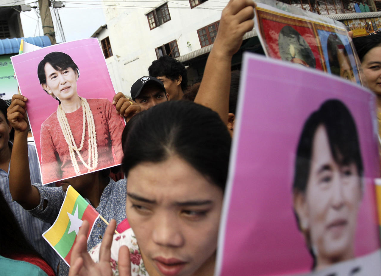 Myanmar workers hold portraits of Myanmar opposition leader Aung San Suu Kyi as they gather to hear her speech in Samut Sakhon, Thailand on Wednesday, May 30, 2012. Kicking off her first trip abroad in nearly a quarter-century, Suu Kyi offered encouragement Wednesday to impoverished migrants whose flight to neighboring Thailand is emblematic of the devastation wrought on her homeland by decades of misrule. (AP Photo/Sakchai Lalit)