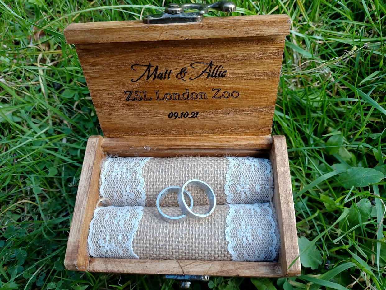 Two silver rings sit within a light brown wooden box on a green background