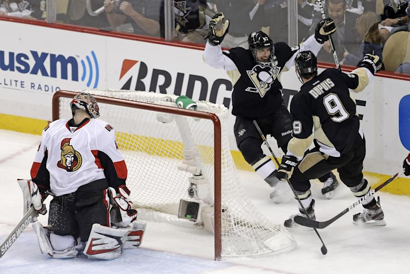 Pittsburgh Penguins' Sidney Crosby (87) celebrates with teammate Pascal Dupuis (9) as Ottawa Senators goalie Craig Anderson (41) reacts to Crosby's second goal of the first period of Game 2 of an NHL hockey Stanley Cup second-round playoff series, in Pittsburgh on Friday, May 17, 2013. (AP Photo/Gene J. Puskar)