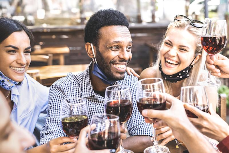 group of young people gather at barbecue drinking wine with masks under their chins