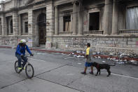 People walk past an area of the Congress building damaged during protests in Guatemala City, Sunday, Nov. 22, 2020. Protesters broke into the building and set it partially on fire amid growing demonstrations against President Alejandro Giammattei and the legislature for approving a controversial budget that cut educational and health spending. (AP Photo/Moises Castillo)