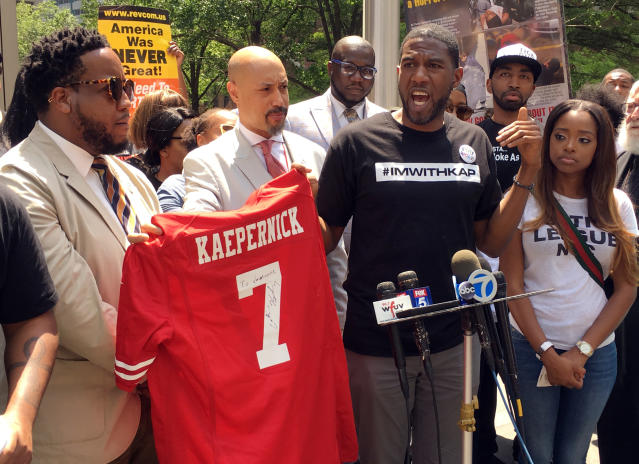 New York Councilman Jumaane D. Williams, second from right, with the help of Kirsten John Foy, second from left, Northeast Regional Director of the National Action Network, holds a jersey with Colin Kaepernick's name on the back, during a rally of civil rights activists outside of the NFLs headquarters, Friday, May 25, 2018, in New York. About 50 people gathered to protest the NFLs new policy aimed at ending player protests during the playing of the national anthem in stadiums before games. Kaepernick, the former San Francisco 49ers quarterback, started the movement of taking a knee during the anthem to protest police brutality and racial inequality two seasons ago. (AP Photo/Ralph Russo)
