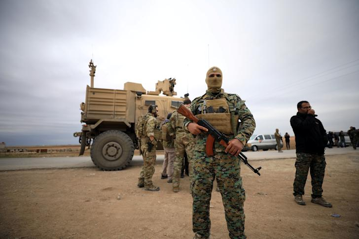 Syrian Democratic Forces and U.S. troops are seen during a patrol near the Turkish border in Hasakah, Syria, last November. (Photo: Rodi Said/Reuters)