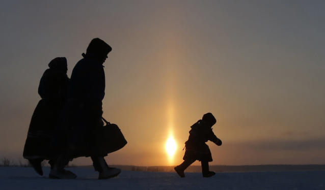 FILE - In this FILE photo taken on Sunday, March 15, 2015, a Nenets family in the city of Nadym, in northern Siberia, Yamal-Nenets Region, 2500 km (about 1553 miles) northeast of Moscow, Russia. In a study published Wednesday Jan. 16, 2019, scientists working on the Global Terrestrial Network for Permafrost, say the world's permafrost is getting warmer, with temperatures increasing by an average of 0.3 degrees Celsius (0.54 Fahrenheit) over a decade. (AP Photo/Dmitry Lovetsky, FILE)