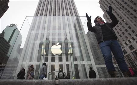 A man poses for a photo in front of the Apple store on 5th Avenue in New York