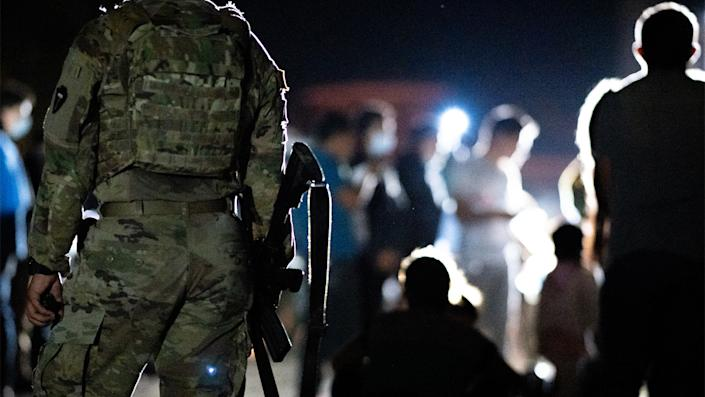 A member of the National Guard stand watch while immigrants wait to be processed after crossing the Rio Grande into the U.S. on June 16, 2021 in Roma, Texas. (Brandon Bell/Getty Images)