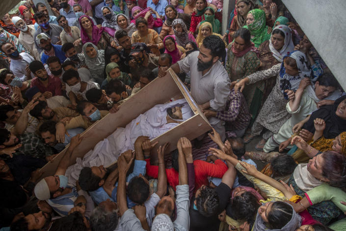 Relatives and neighbors lift the coffin of Waseem Ahmed, a policeman who was killed in a shootout, during his funeral on the outskirts of Srinagar, Indian controlled Kashmir, Sunday, June 13, 2021. Two civilians and two police officials were killed in an armed clash in Indian-controlled Kashmir on Saturday, police said, triggering anti-India protests who accused the police of targeting the civilians. (AP Photo/ Dar Yasin)