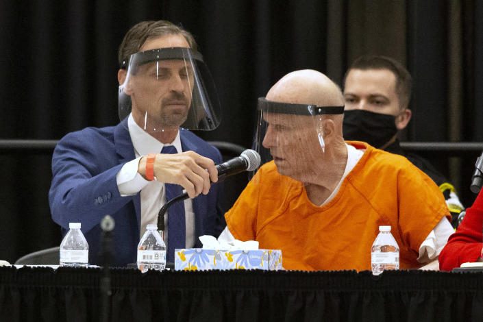 Joseph Cress, left, the public defender for Joseph James DeAngelo, charged with being the Golden State Killer, adjusts the microphone for his client during a hearing in Sacramento Superior Court in Sacramento, Calif. Monday June 29, 2020. DeAngelo, 74, pleaded guilty to 13 counts of murder and multiple other charges 40 years after a sadistic series of assaults and slayings in California. Due to the large numbers of people attending, the hearing was held at a ballroom at California State University, Sacramento to allow for social distancing. (AP Photo/Rich Pedroncelli)