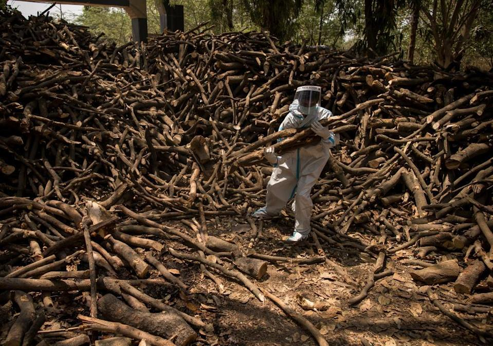 Cemetery workers wearing PPE sort logs for funeral pyres, to perform the last rites for patients who died of Covid, on 22 April at a crematorium in the outskirts of New Delhi, India
